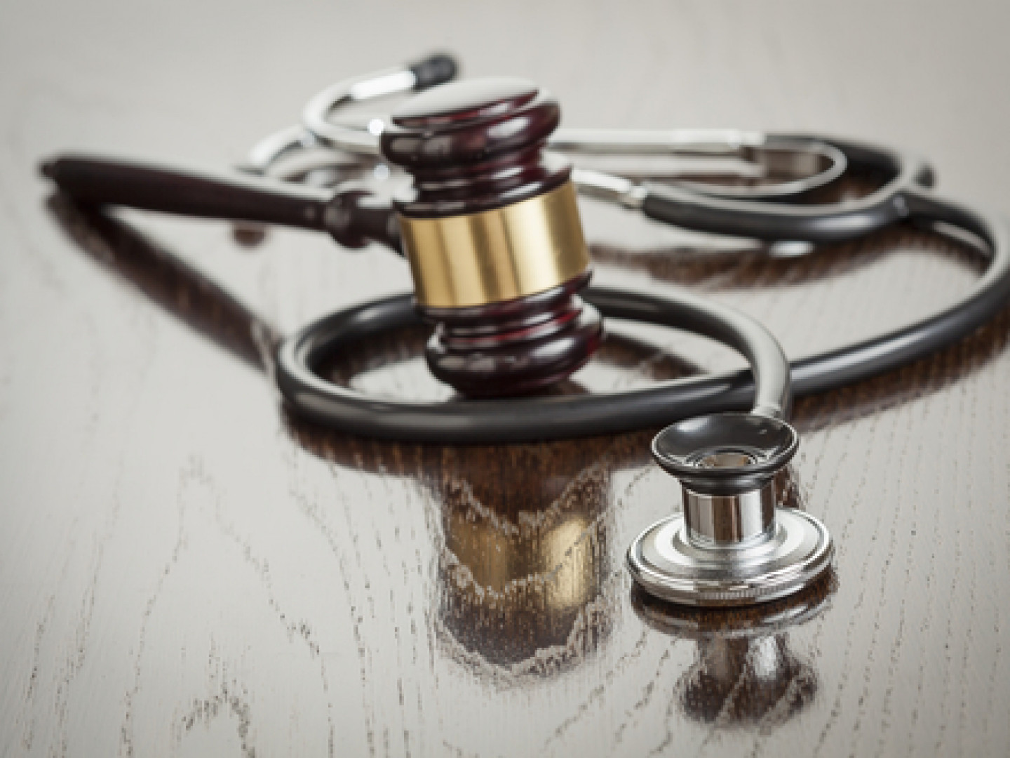 Stethoscope on a table wrapped around a gavel